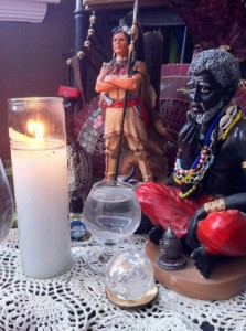 Statues depicting Indian and Congo spirits grace this simple bóveda along with a glass of water, crystal ball and a white candle.