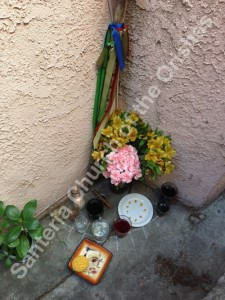The Lucumí Ancestral Shrine at our church with offerings of flowers, food, drinks and cigar.